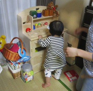 toddler playing at a toy stove