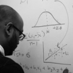 Neal Patel working on equations at a white board.