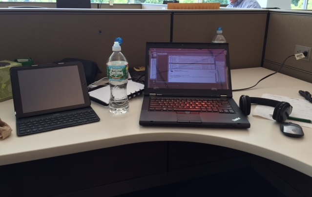 An image from the photo diary of a study participant working at a temporary desk at a client site, with laptop and tablet handy.