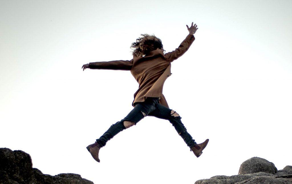 woman jumping across a gap in rocks