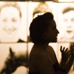 two silhouetted women talking in front of photographs of women, horse